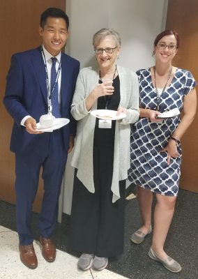 Albert Yu and program directors standing together smiling and eating cake.