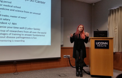 Dr. Stephanie Eisenbarth Standing next to a podium, lecturing in front of her power point slides