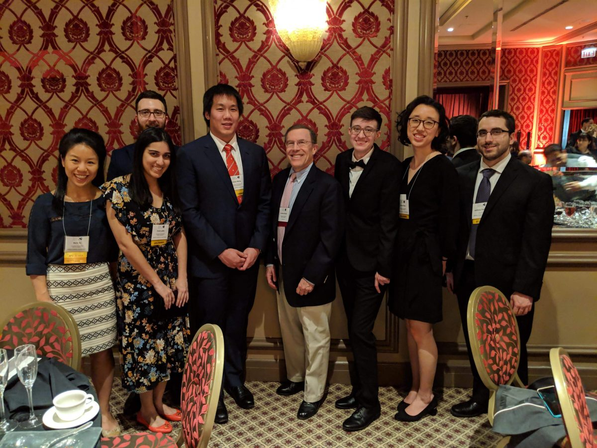 UConn MD/PhD students standing together smiling, nicely dressed in a fancy ballroom