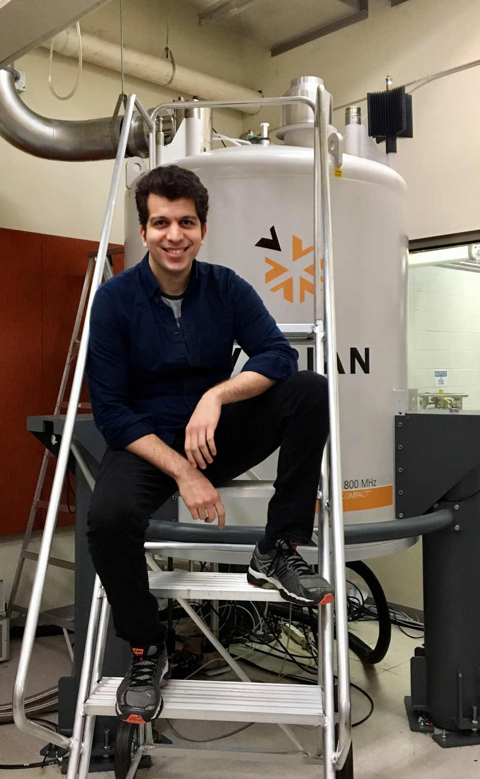 Gianluca Arianna smiling, seated in front of biophysics equipment